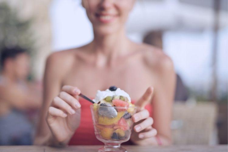 Девушка с фруктовым салатом в кафе