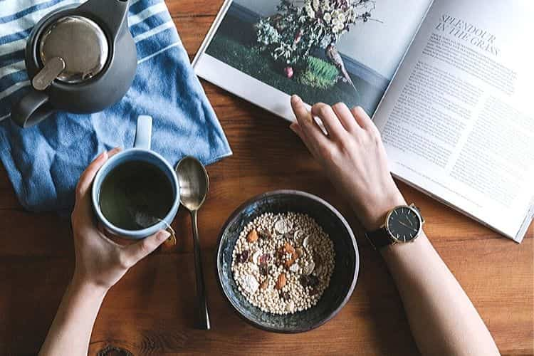 Девушка читает книгу во время завтрака